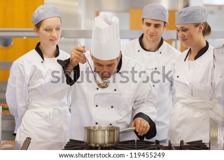 Class watching teacher taste the soup in the kitche - stock photo