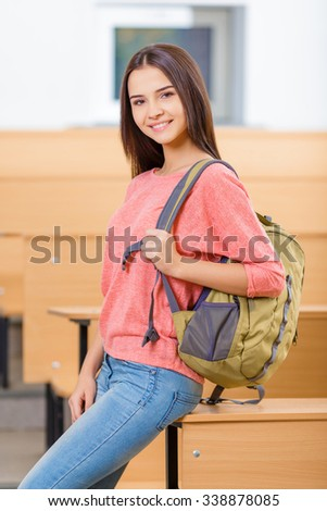 Classes time. Smiling young girl standing near the desk while holding her backpack - stock photo