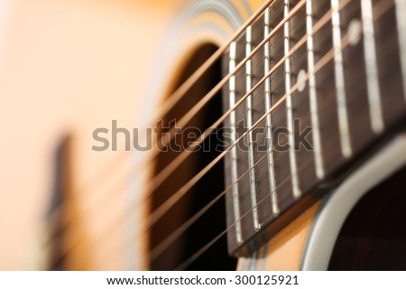 Classic acoustic guitar at weird and unusual perspective closeup. Six strings, free frets, sound hole and soundboard. Musical instruments shop or learning school concept - stock photo