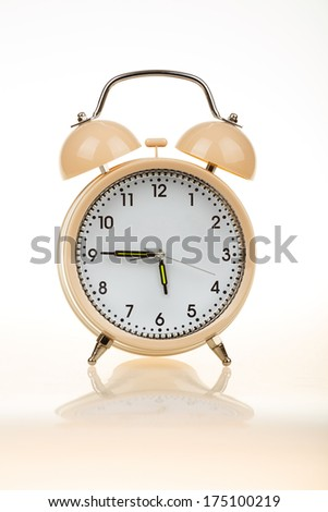 classic alarm clock on white table with reflection