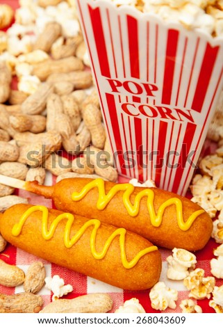 Classic American baseball park snack including two delicious corn dogs with piles of popcorn and peanuts - stock photo