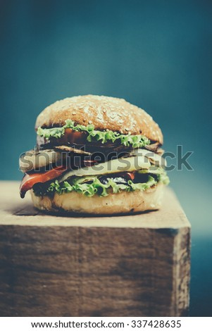 Classic american burger on wooden board. Toned picture. Selective focus and shallow DOF - stock photo