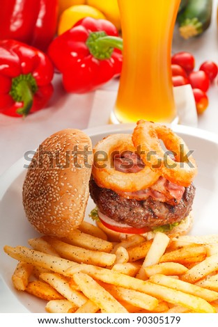 classic american hamburger sandwich with onion rings and french fries,glass of  beer and fresh vegetables on background, - stock photo