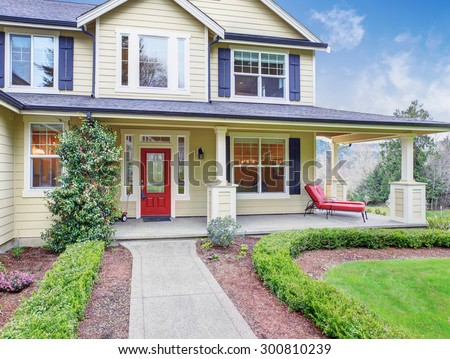 Classic american home with yellow exterior, and blue trim. also a red door. - stock photo