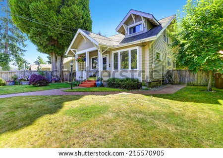 Classic american house entrance porch, decorated with hanging flower pots. Tile brick walkway and lawn. - stock photo