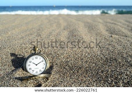 Classic Analog Clock In The Sand On The Beach Near The Ocean - stock photo