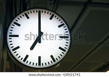 Classic analog clock point at 7 o'clock with dark background - stock photo