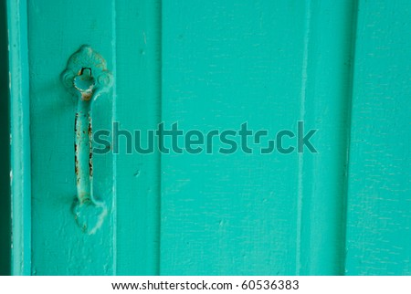 Classic antique metal door handle painted teal, now chipped and rusted on wooden door. - stock photo