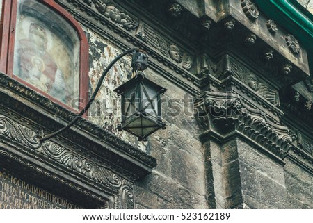 Classic architecture. Old lantern. Dark stone facade. Angels faces. Decor. Icon
