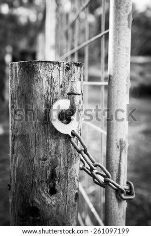 Classic Australian farm gate lock on a wooden post in black and white - stock photo