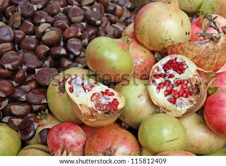 classic autumn fruits with many ripe chestnuts and pomegranates - stock photo