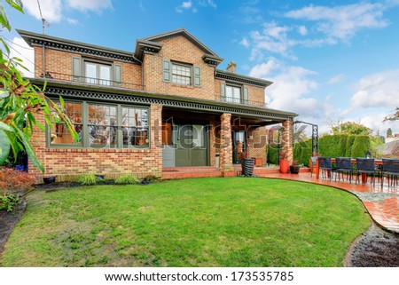 Classic backyard column porch of a stoned two story house - stock photo