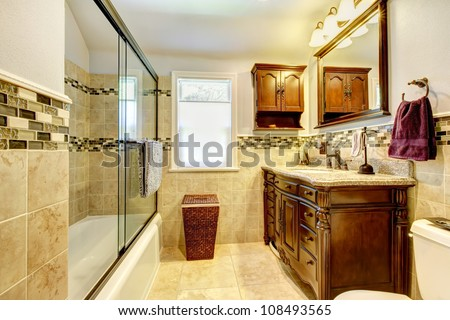 Classic bathroom with natural stone tiles and wood cabinet. - stock photo