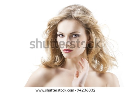 classic beauty portrait of young sexy girl with hairstyle and flying hair from wind. She is turned of three quarters at right, looks in to the lens and has the right hand near the face. - stock photo