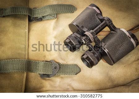 Classic binoculars on green rucksack - stock photo