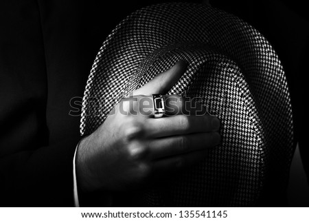 Classic black and white close-up photograph of a male hand wearing premium ring and holding a stylish hat - stock photo