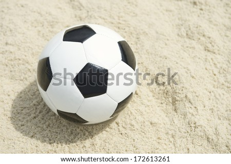 Classic black and white football soccer ball sits on sand beach background in Rio de Janeiro Brazil - stock photo