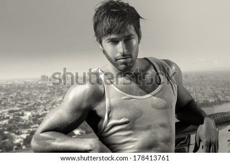 Classic black and white portrait of a young handsome man above city skyline - stock photo