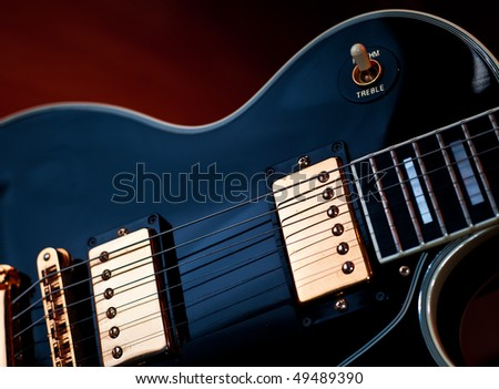 Classic black Les Paul rock and roll or jazz style guitar. Soft blue lighting on guitar and warm background light creates stage or studio performance atmosphere. - stock photo