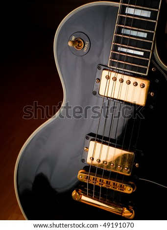 Classic black Les Paul style rock and roll guitar. Soft lighting on instrument for a stage or studio atmosphere. - stock photo