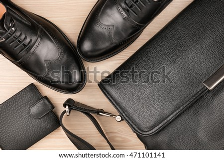 Classic black shoes, briefcase and purse on the wooden floor, can be used as background