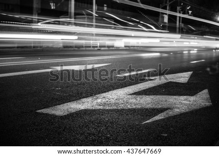 Classic Black & White style - Nights lights of the big city, the night avenue with road markings and headlights of the approaching cars, close up view from asphalt level.