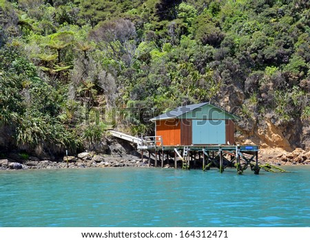 Classic boat house and jetty on the rocky shores of the Marlborough Sounds, New Zealand. - stock photo