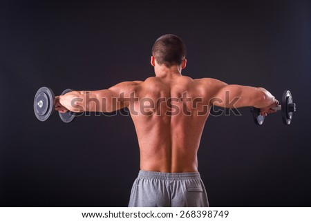 Classic bodybuilder, posing on a black background. Athletic man showing his muscle in suspense. Sports, strength, bodybuilding, physical strength. - stock photo