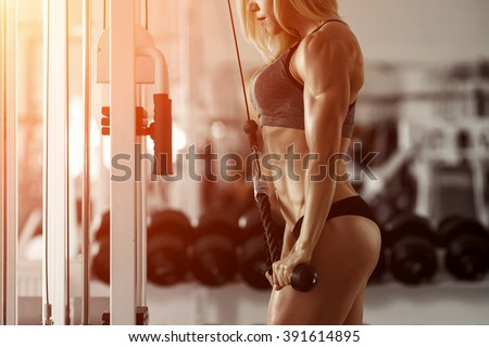 Classic bodybuilding. Muscular blonde fitness woman doing exercises in the gym. Fitness - concept of healthy lifestyle. Fitness woman in the gym. Crossfit woman. Bodybuilder woman in the gym. - stock photo