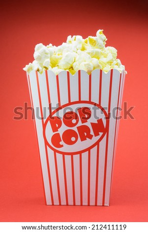 Classic box cinema popcorn on red background  - stock photo