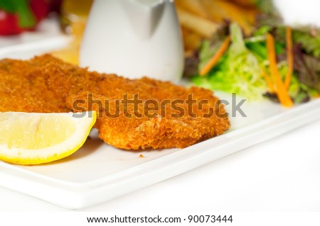 classic breaded Milanese veal cutlets with french fries and vegetables on background - stock photo