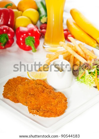 classic breaded Milanese veal cutlets with french fries , vegetables and glass of lager beer on background - stock photo