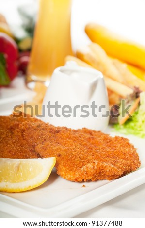 classic breaded Milanese veal cutlets with french fries , vegetables and glass of lager beer on background , - stock photo