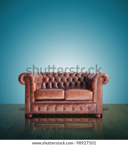 Classic Brown leather sofa and old blue background.