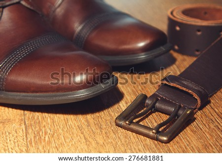 classic brown shoes and belt on wooden table. vintage picture