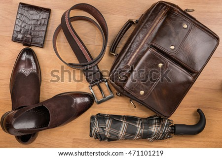 Classic brown shoes, briefcase, belt and umbrella on the wooden floor, can be used as background