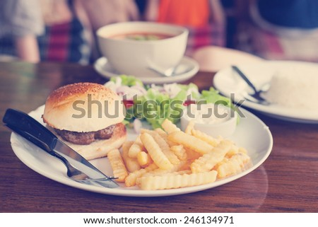 classic burger with French fries on the table in a cafe. Retro toning - stock photo