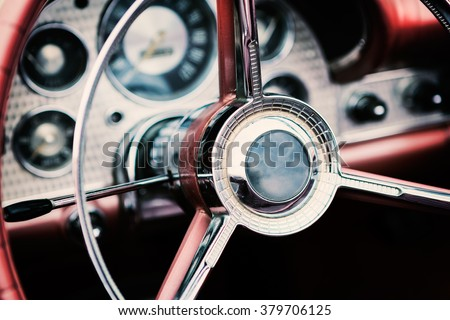 Classic car interior with close-up on steering wheel - stock photo
