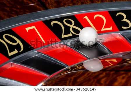 Classic casino roulette wheel with black sector twenty-eight 28 and white ball and sectors 29, 7, 12, 35 - stock photo