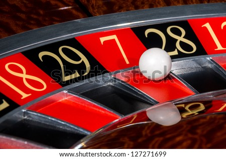 Classic casino roulette wheel with lucky red sector seven 7 and white ball - stock photo