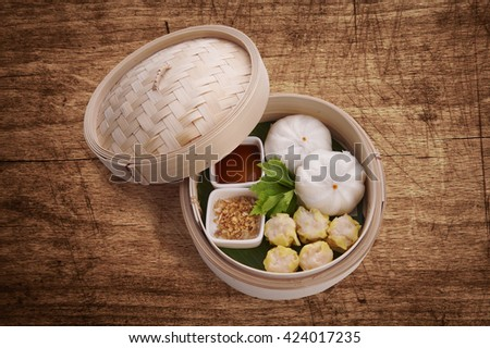 Classic Chinese style Canton cuisine - pork steamed dumpling or dim sum along with Chinese bun served in small steamer basket on wood background - stock photo