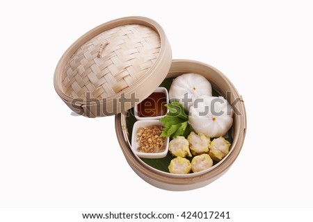 Classic Chinese style Canton cuisine - pork steamed dumpling or dim sum along with Chinese bun served in small steamer basket on white background - stock photo