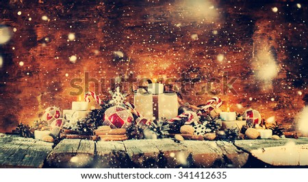 Classic Christmas Composition. Box with Candles, Balls, Toys, Pine Cones, Walnuts on Wooden Background. Drawn Snow. Dark toned - stock photo