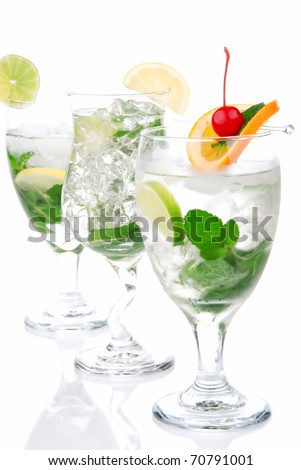 Classic Citrus Mojito cocktails with light rum, vodka, gin, lime, spring of mint, simple soda, orange, maraschino cherry and syrup in cocktail glasses isolated on a white background - stock photo
