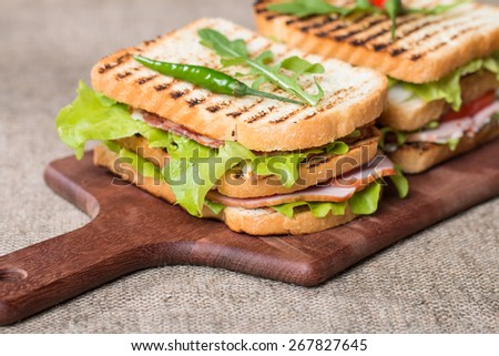 Classic club sandwich with bacon and vegetables on wooden chopping board - stock photo