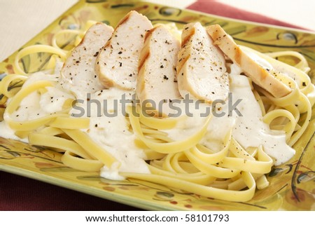 Classic creamy fettuccine alfredo topped with slices of grilled chicken breast. - stock photo