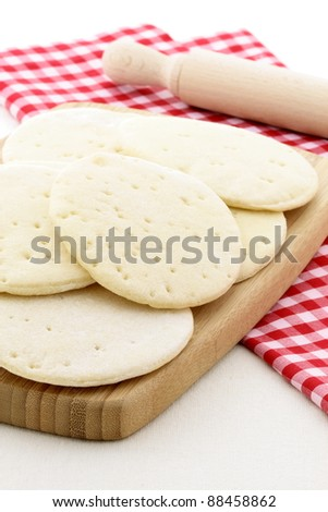 Classic delicious pizza dough on wood cutting board - stock photo
