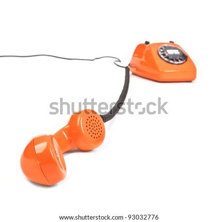classic dial phone on white background, focus set in foreground - stock photo