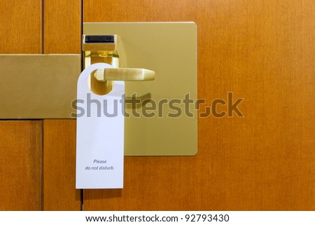 classic do not disturb sign on brass and wood hotel room door cleaned with copyspace for your text - stock photo