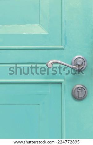 classic door handle on blue door - stock photo